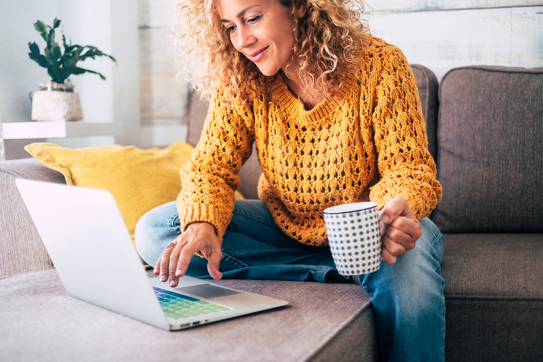 woman laughing while on laptop